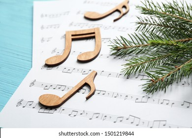 Christmas tree branch, notes and music sheets on blue wooden table