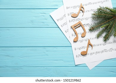 Christmas tree branch, notes and music sheets on blue wooden table, flat lay with space for text