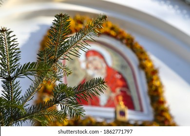 Christmas tree branch on the background of the Orthodox icon and the cross. Orthodox Church Winter - Christmas. The concept of Orthodoxy