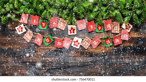 Christmas tree branches with Advent calendar on dark wooden background. Vintage style toned picture with falling snow
