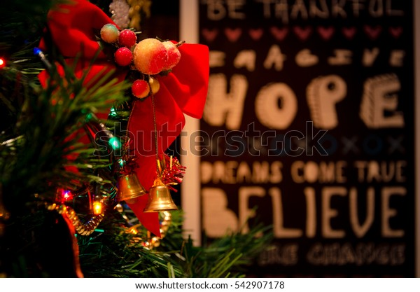 Christmas tree branches with background of a wall sticker with wishes.