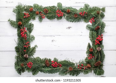 Christmas tree branches with cones and berries on wood background