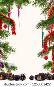 Christmas tree branches decorated with colorful ornaments and pine cones framed on off-white background with copyspace in the center