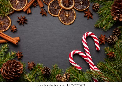 Christmas tree branches on black background as template for a christmas card