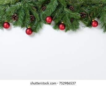 Christmas tree branches and ornaments on white background. Plenty of copy space available.