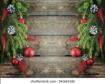 Christmas tree branches and red balls on wooden table with place for your text