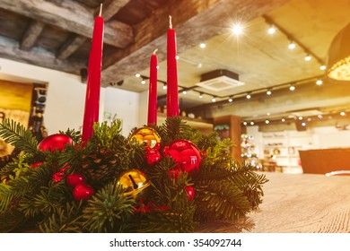 Christmas tree branches, red candles. Christmas decorations on table