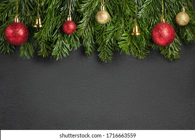 Christmas tree branches with red decorations on a black background. Template for greeting card or design. Horizontal banner with copy space