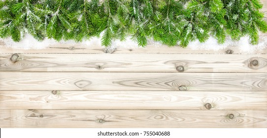 Christmas tree branches with snow decoration on wooden texture. Winter holidays background