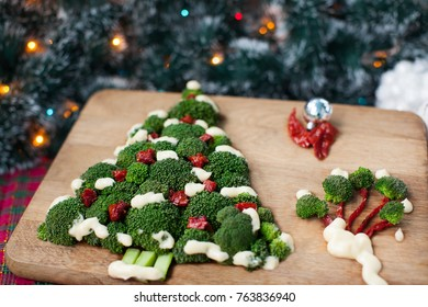 Christmas tree of broccoli green with tomatoes on a wooden dinette on a green background with lights