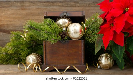christmas tree brunch with golden decoration, vintage wooden box and red christmas flower poinsettia