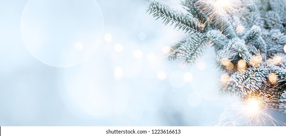 Christmas tree in cold frosty winter background with bokeh and sparklers