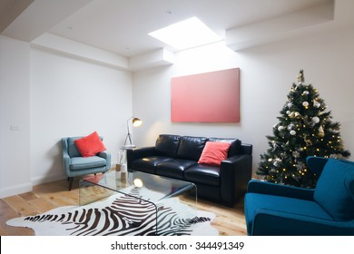Christmas tree in contemporary living room in Australian home with coral detail cushions