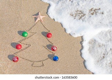 Christmas tree contour with decorations, star and wave on the beach - holiday vacation concept