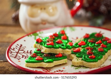 Christmas Tree Cookies Close Up On Holiday Plate By Warm Glowing Light Fire Background.