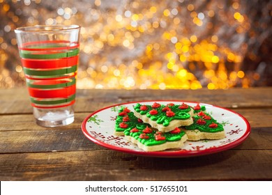 Christmas Tree Cookies On Holiday Plate With Empty Milk Cup By Warm Glowing Light Fire Background.