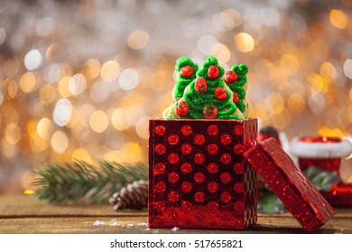 Christmas Tree Cookies In Red Holiday Gift Box By Warm Glowing Light Fire Background With Copy Space.