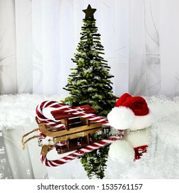 Christmas tree covered with snow next to the sled, Santa's hat and Santa's cane on a white background and reflected in the mirror.