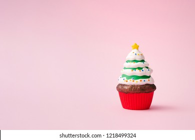 Christmas tree cupcake on pink background with copy space. Minimal Christmas theme. New year food concept.