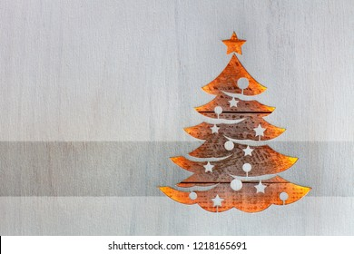 Christmas tree cut out from white painted wooden board letting warm ligths shine through - seasonal and holidays card, copy space