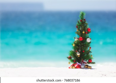 Christmas tree decorated with colourful baubles and presents underneath it, stands on a beautiful sandy beach with background blur of the ocean and sky.