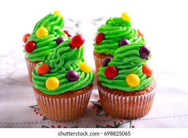Christmas tree decorated cupcakes on table cloth