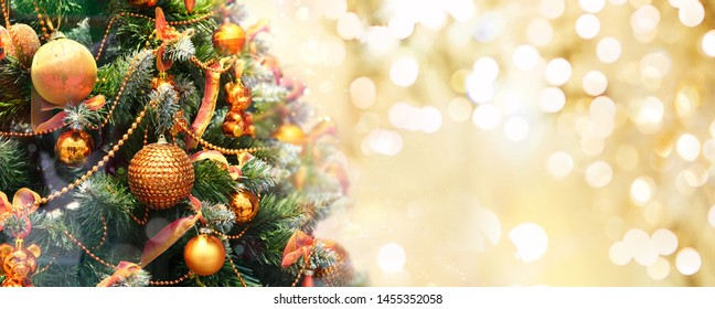 Christmas tree decorated with Golden balls toys on a blurred, sparkling and fabulous fairy background with beautiful bokeh, copy space.