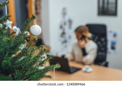 Christmas tree decorated in the office, business women in blur background working on laptop