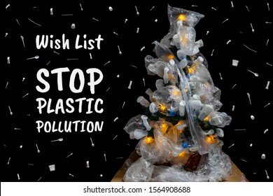 Christmas tree decorated with plastic bags. The wish list is to stop plastic pollution. Christmas snow from disposable tableware. Black isolated background. New year concept of environmental pollution
