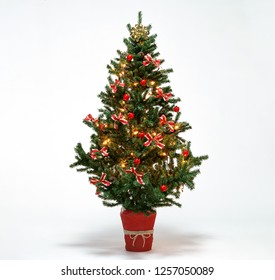Christmas tree decorated with red baubles and ribbon bow on white background