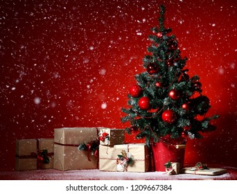 Christmas tree decorated with red patchwork ornament balls and craft presents gifts for new year 2019  under heavy snow on dark red background