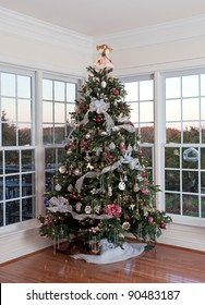Christmas tree decorated with silver and white ribbons and ornaments in family home