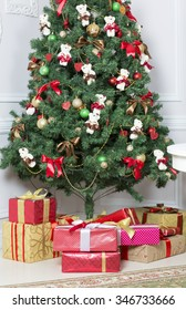 Christmas tree decorated with toys. Gifts lie under the tree.