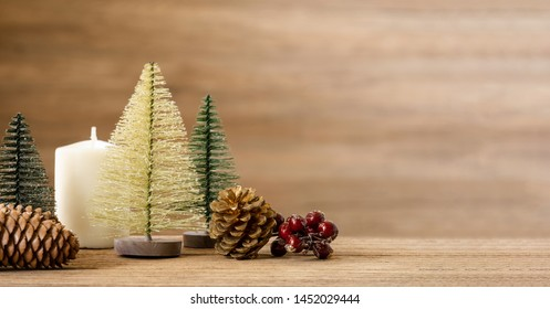 Christmas tree decoration background on wood table with snow.pine cone,mistletoe and bell ball hanging with blur wood wall background.Holiday greeting card banner