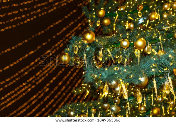Christmas tree decoration with lights. Selectable focus with beautiful gold bokeh and blur. Festive xmas background.