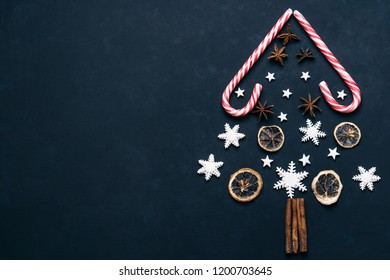 Christmas tree decoration made of candies and spices on black background with copy space. Creative poster template, DIY, winter holidays celebration concept