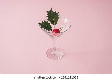 Christmas tree decoration in martini glass on pastel pink background with creative copy space. New year or Christmas eve party concept.