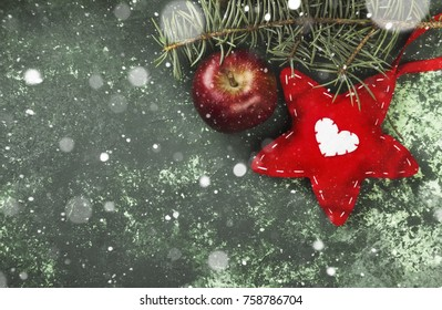 Christmas tree, decoration with a red star and an apple on a green background. Top view, copy space. Snow