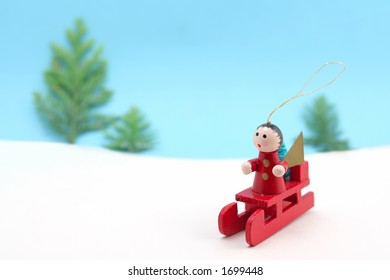 A Christmas tree decoration sets off across a snowy landscape on a sledge
