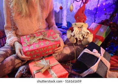 Christmas tree decoration and woman holding toy gifts, closeup