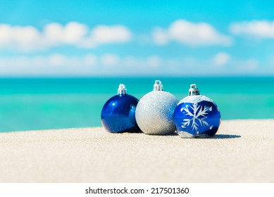 Christmas tree decorations on sea beach sand - winter holidays in hot countries concept