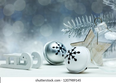 christmas tree decorations, wooden star and glass ball on grey background with blurred fir tree branch and lights