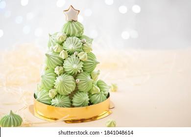Gâteaux en dessert à l'arbre de Noël faits de meringues vertes avec des décorations de canne à sucre sur fond de lumières défocalisées.