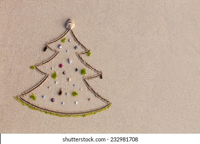 Christmas tree drawn on the sand and decorated with seashell and algae