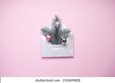 Christmas tree in an envelope, minimal New Year card. Fir tree branch with colored Christmas balls on a pink background.
