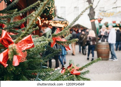 Christmas tree or fir branches in the foreground. The Christmas market in Germany is blurred in the background. Vacation. People relax during the holidays.