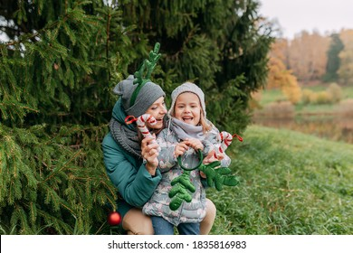 Christmas tree fir branches. Mother and daughter decorate christmas tree outside. Decorative antlers on had. Christmas decorations.