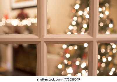Christmas tree and fireplace mantle through a window.  Shallow depth of field so tree and chimney mantle are out of focus.