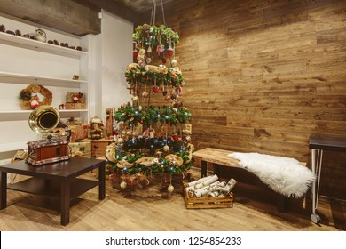 Christmas tree, firewood and gramophone in loft studio interior. Wooden walls, simple design