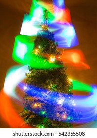 a Christmas tree and flying multicolored lights in a long exposure